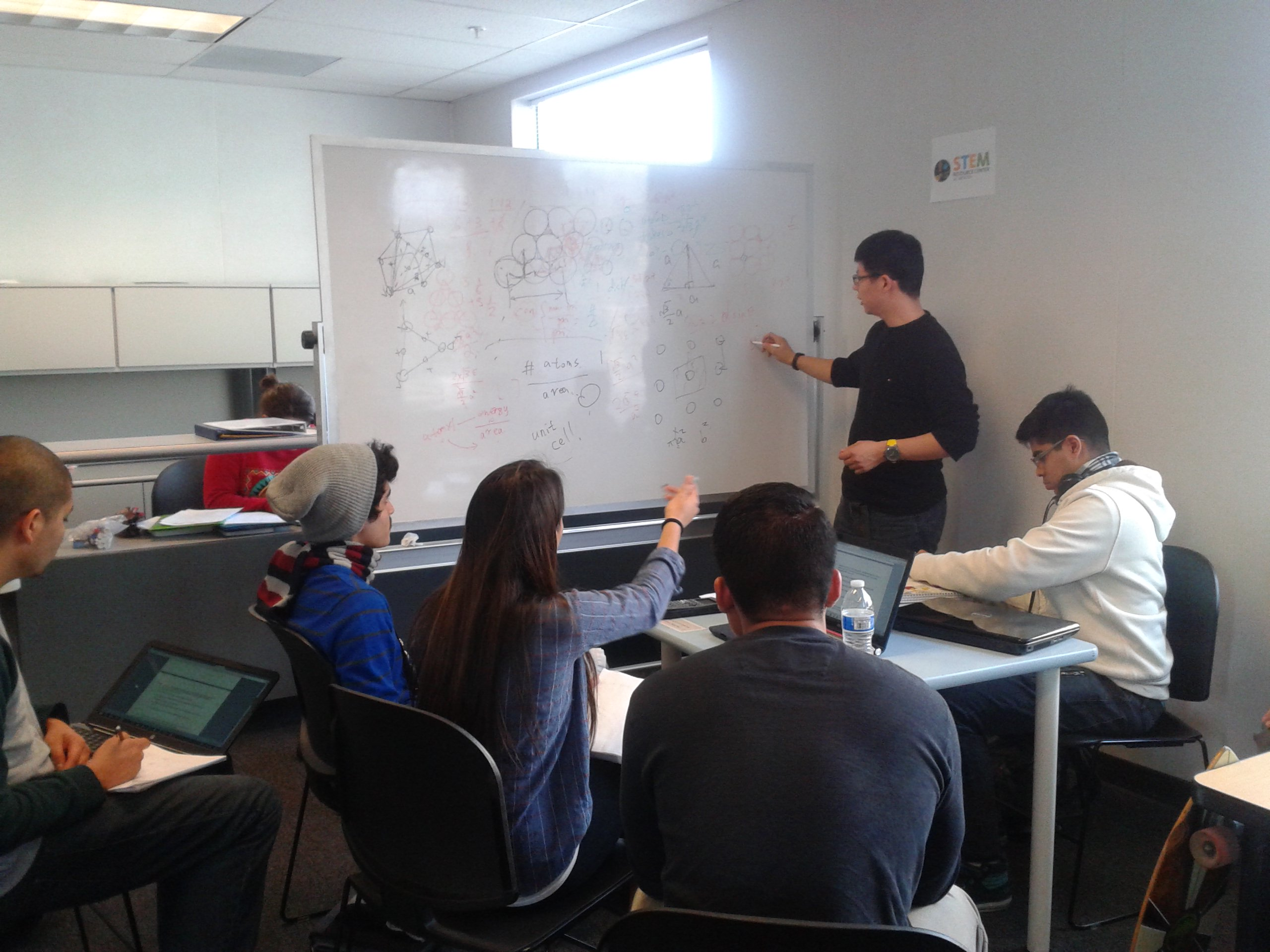 Students in class with professor writing on whiteboard
