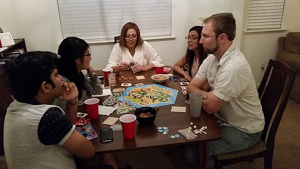 Photo of partners playing Settlers of Catan at Game Night